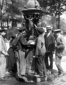 Personnes se désaltèrant à une fontaine Wallace à Paris. Photo by unknown (1911). Bibliothèque nationale de France. PD: Domaine Public. PD-US. Wikimedia Commons.